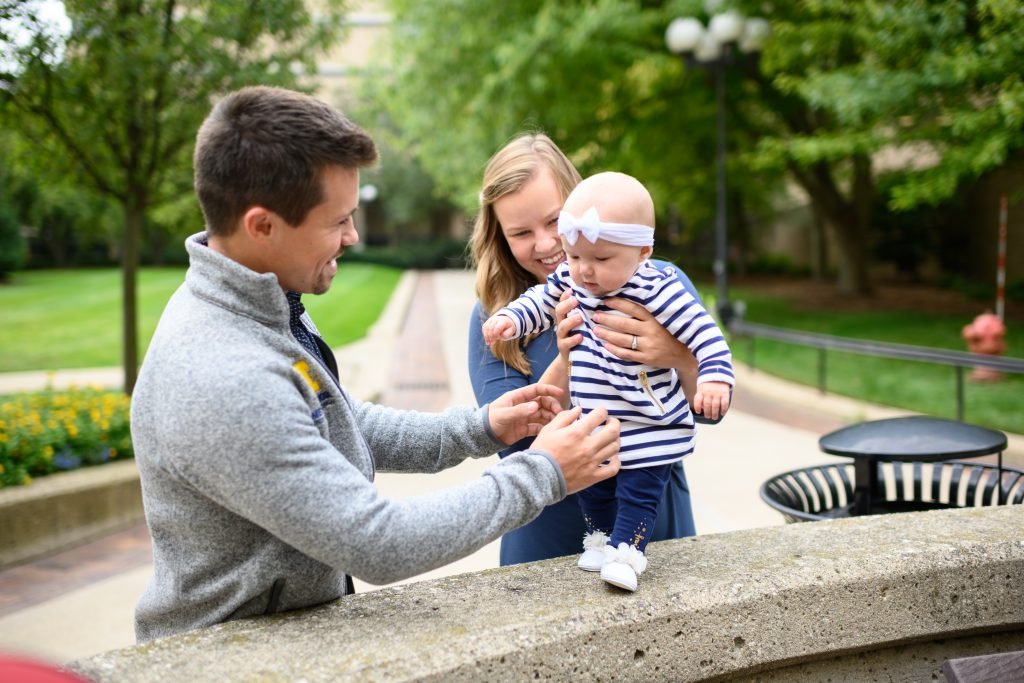 Medical student scholarship recipient Ross Michaels, his wife Kaitlyn, and their daughter in the University Hospital courtyard.