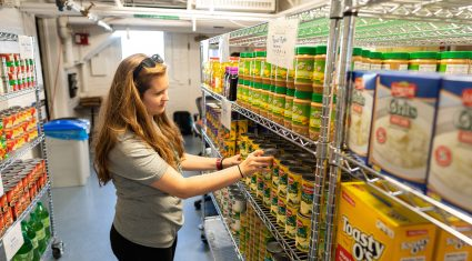 Worker stocks canned goods on the shelves