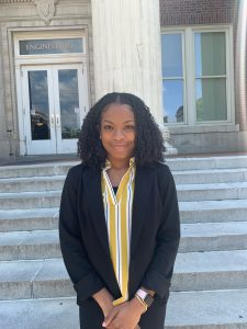 Featured engineering student, Kori Maxie, in front of campus building