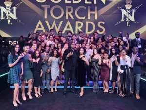 Kori and a group of students pose for a photo at an awards ceremony