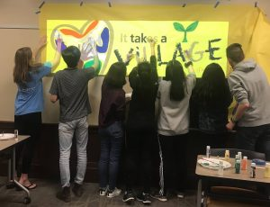 "Neal with a group of community volunteers hanging a sign that says ""it takes a village."""