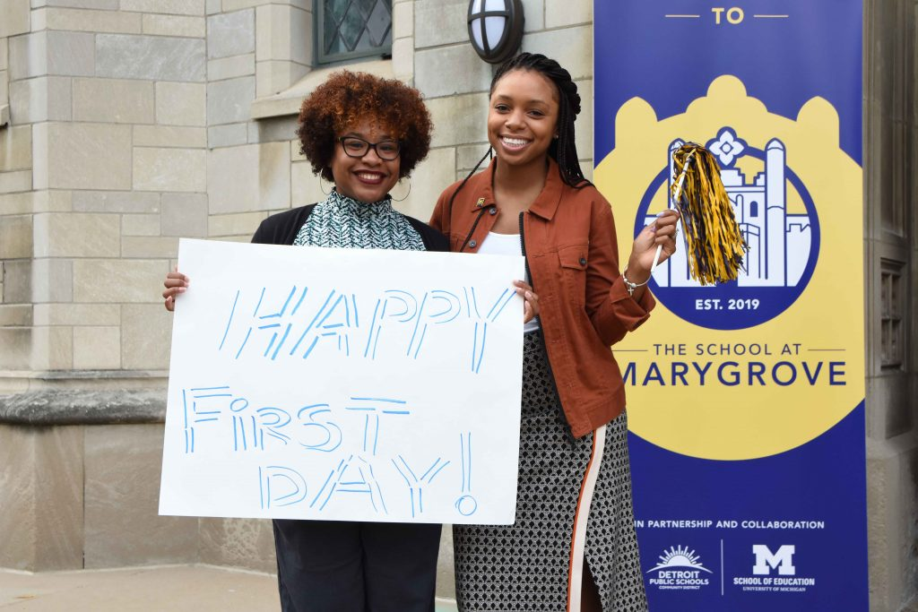 """Two doctoral students in front of the School at Marygrove holding a sign that says """"Happy first day!"""""""