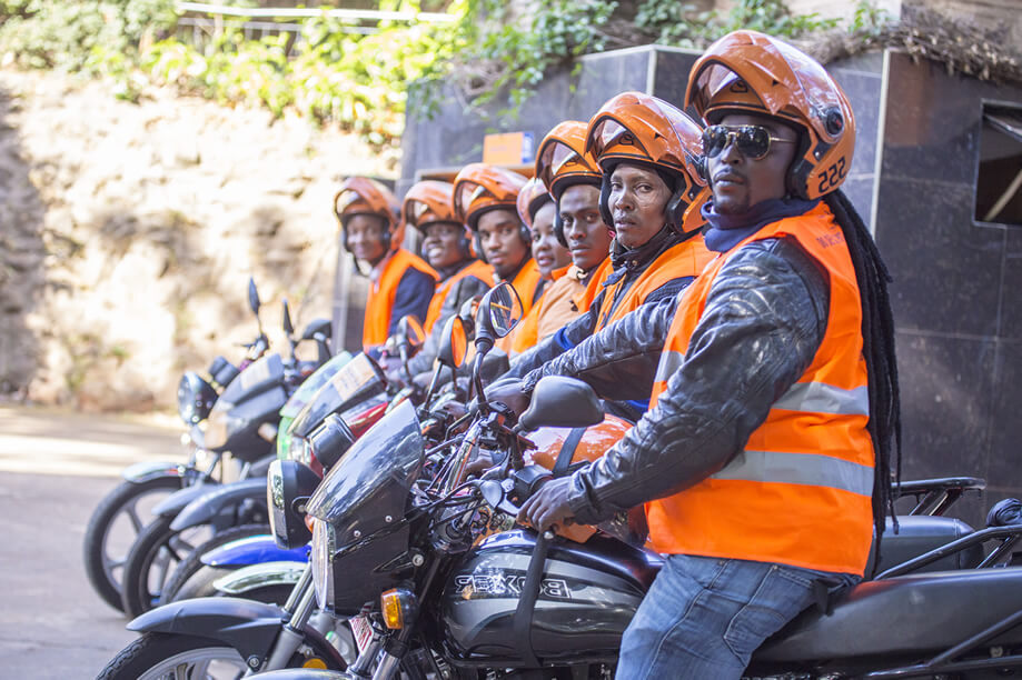 SafeBoda drivers posing on their motorcycles.
